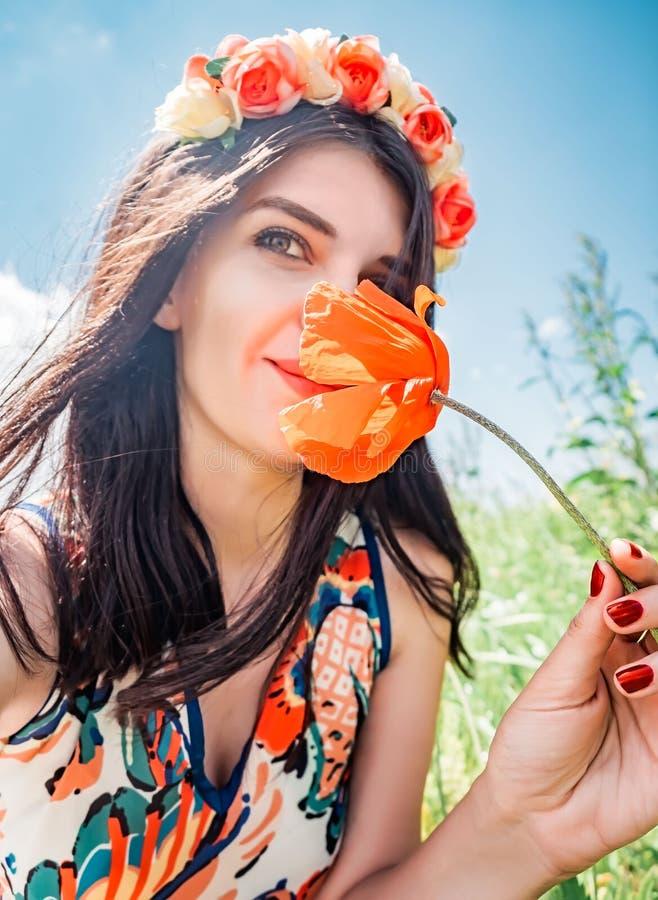 Junge schöne glückliche Frau im Blumenkranz inhaliert das Aroma einer Mohnblumenblume Hübsche Frau mit einer roten Mohnblumenblum lizenzfreies stockbild