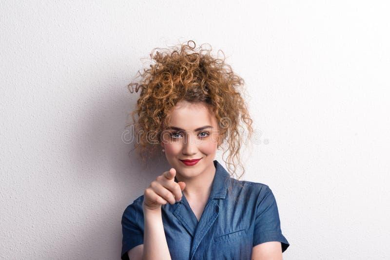 Junge schöne glückliche Frau im Studio, zeigend auf Sie lizenzfreies stockbild
