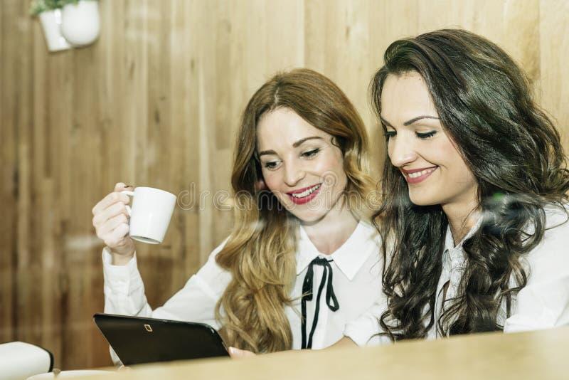 Junge schöne glückliche Frauen, die Tablette verwenden lizenzfreie stockfotos