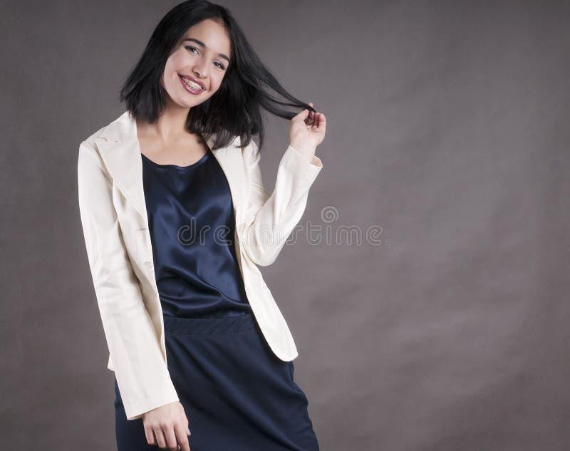 Junge schöne glückliche Geschäftsfrau stützt Brunettestudio ab stockfotografie