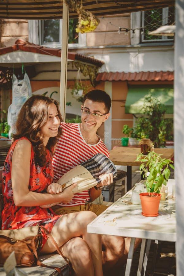 Junge schöne glückliche liebevolle Paare, die am Straßenfreiluftcafé, Spaß mit Kissen habend sitzen Anfang der Liebesgeschichte v stockbilder