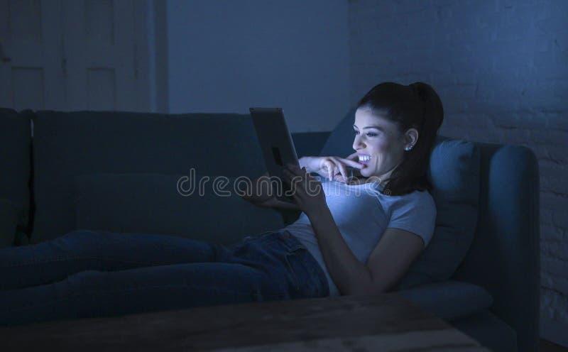 Junge schöne glückliche und entspannte lateinische Frau 30s, die auf der Hauptcouch Spät- unter Verwendung des digitalen Gerätlap lizenzfreies stockbild