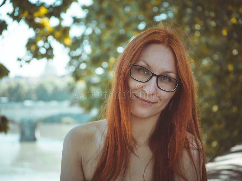 Junge schöne hübsche Frau mit dem roten Haar und den Gläsern, die auf der Straße von Rom, Italien aufwerfen stockfotografie