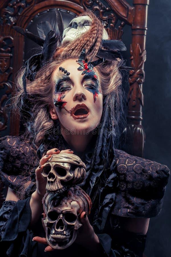 Junge schöne Hexe sitzt auf einem Stuhl Hell bilden Sie, Schädel, Rauchhalloween-Thema lizenzfreie stockbilder
