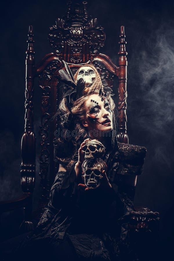 Junge schöne Hexe sitzt auf einem Stuhl Hell bilden Sie, Schädel, Rauchhalloween-Thema stockfotos