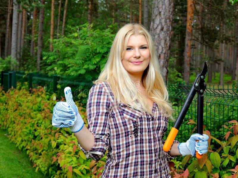 Junge schöne im Garten arbeitende und trimmende Frau stockbilder