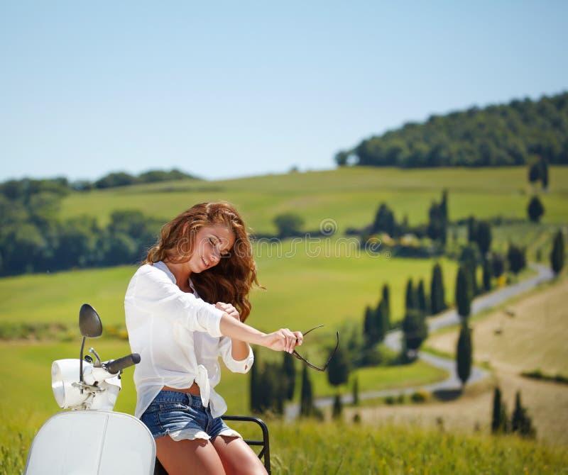 Junge schöne italienische Frau, die auf einem Roller sitzt stockfoto