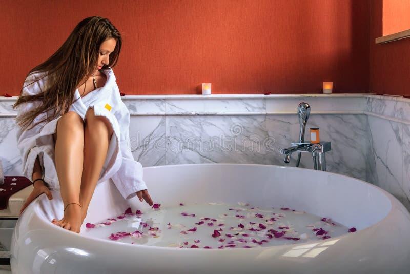 Junge schöne kaukasische Frau im weißen Bademantel ist im Begriff, sich im Whirlpool mit den rosafarbenen Blumenblättern zu entsp stockfoto