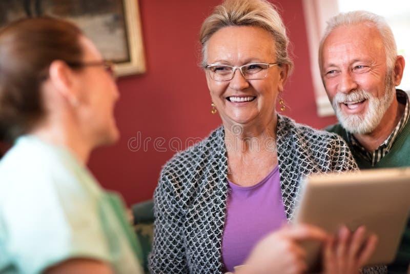 Junge schöne Krankenschwester wenden Sorgfalt über alte Leute an stockfoto