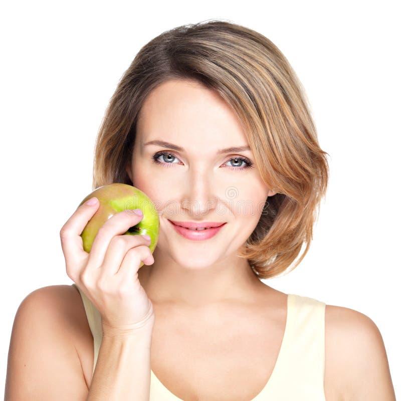 Junge schöne lächelnde Frau berührt den Apfel, um gegenüberzustellen. stockfotografie