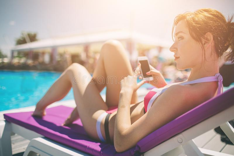 Junge schöne lächelnde Frau im Bikini im warmen Pool auf Erholungsort und Gespräch im Handy stockbilder