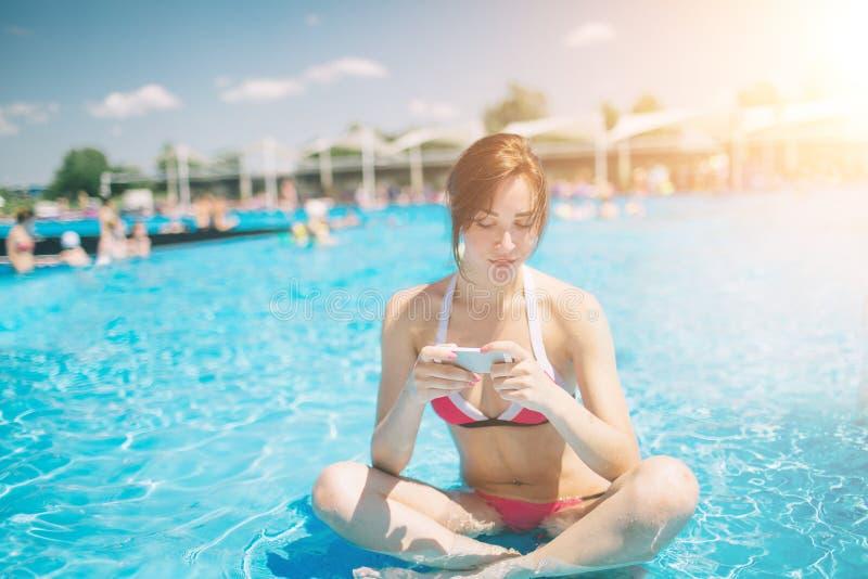 Junge schöne lächelnde Frau im Bikini im warmen Pool auf Erholungsort und Gespräch im Handy stockfotografie