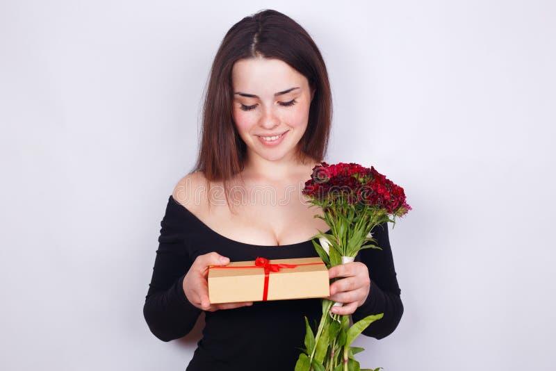Junge schöne lächelnde Frau mit Blumen und Geschenk Datierung, rel stockfotos