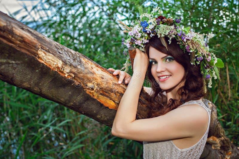 Junge schöne lächelnde Frau mit Blumenkranz lizenzfreie stockfotos