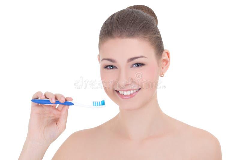Junge schöne lächelnde Frau mit der Zahnbürste lokalisiert auf Weiß lizenzfreies stockbild