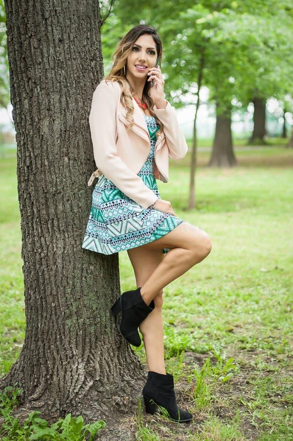 Junge schöne lächelnde Frau unter Verwendung der Mobiltelefone auf allgemeinem Park lizenzfreies stockfoto