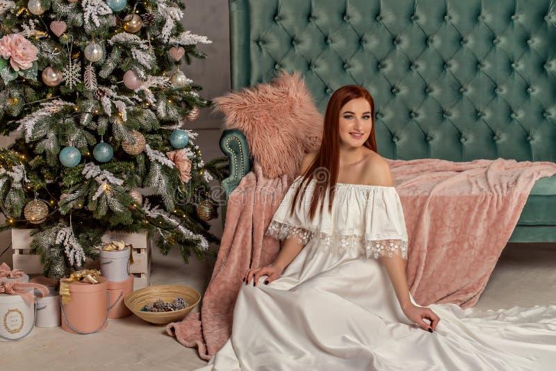 Junge schöne Lächelnfrau im weißen eleganten Abendkleid, das auf Boden nahe Weihnachtsbaum und Geschenken sitzt Innenraum mit Chr lizenzfreie stockfotografie