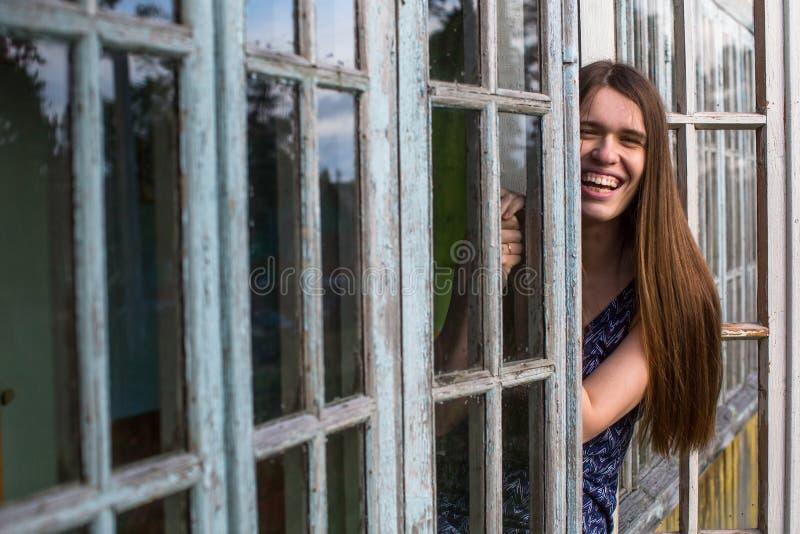 Junge schöne langhaarige Frau, die auf dem Fenster sitzt stockfotografie