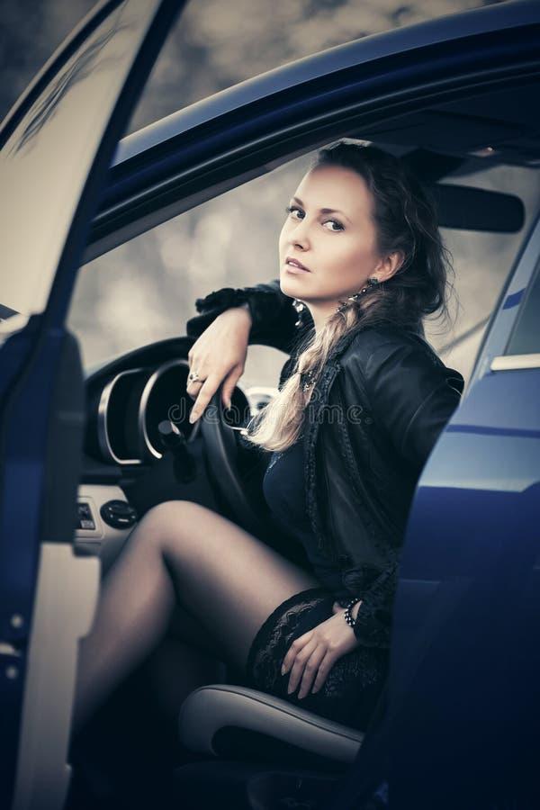 Junge schöne Modefrau, die in einem Auto sitzt stockfotografie