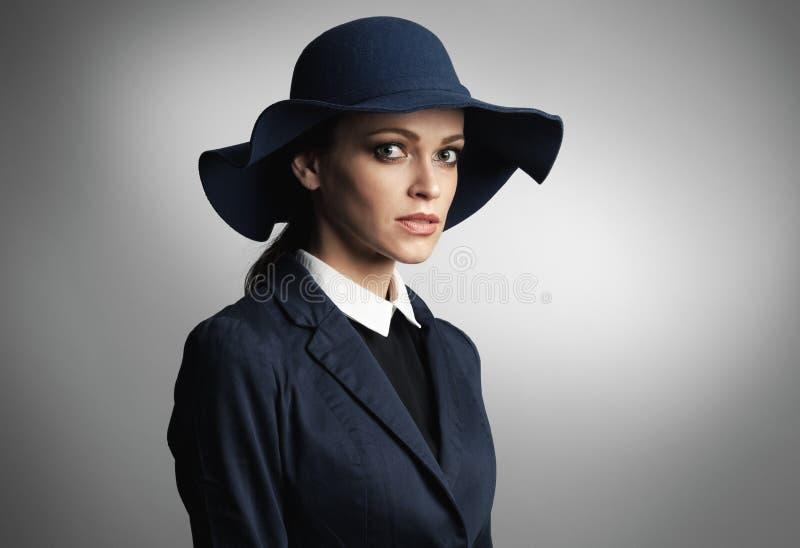 Junge schöne moderne Frau, die einen Hut trägt stockfotografie