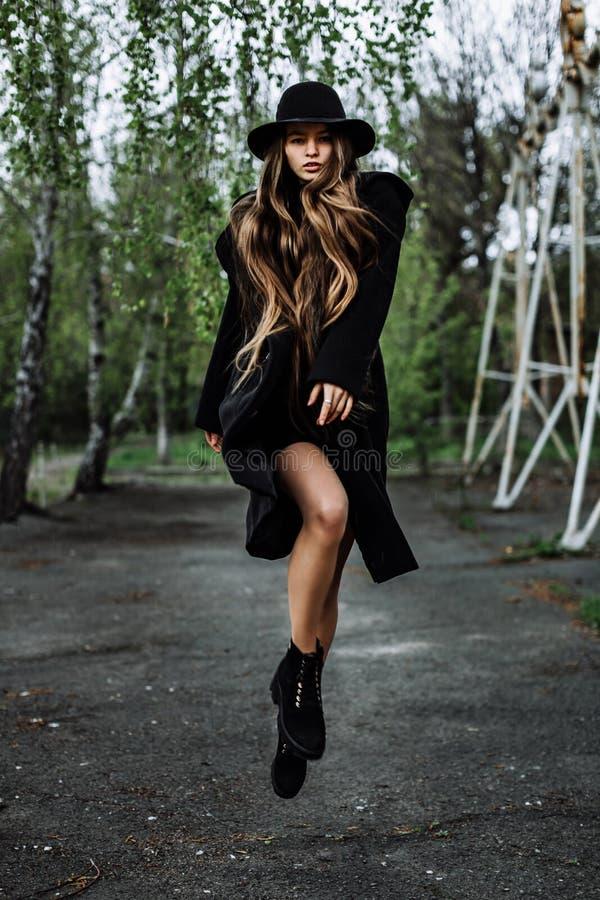 Junge schöne moderne Frau im Hut schweben, langes Haar frei stockfotografie