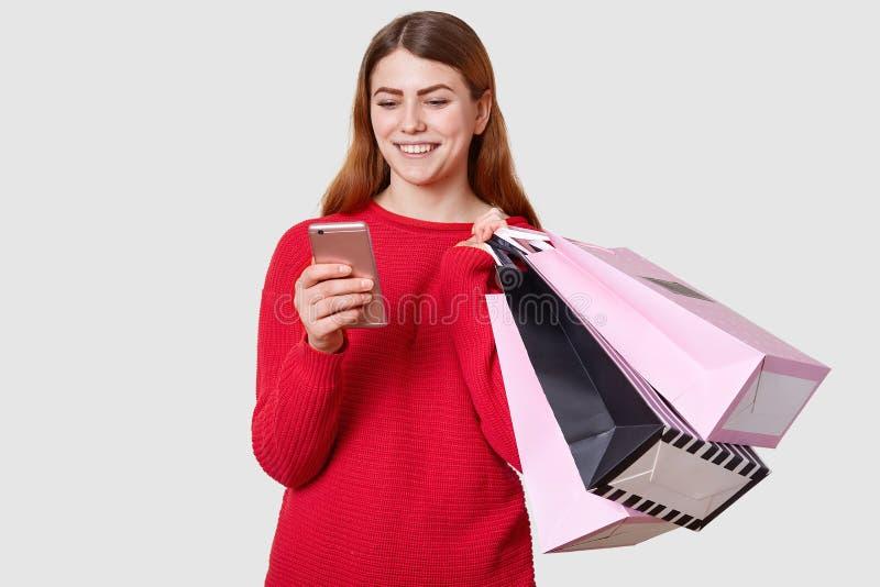 Junge sch?ne moderne kaukasische Frau h?lt Einkaufstaschen in einer Hand und in Smartphone in einem anderen lokalisiert auf wei?e lizenzfreies stockfoto