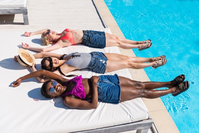 Junge schöne multiethnische Frauen, die am Poolside liegen und stillstehen stockfotos