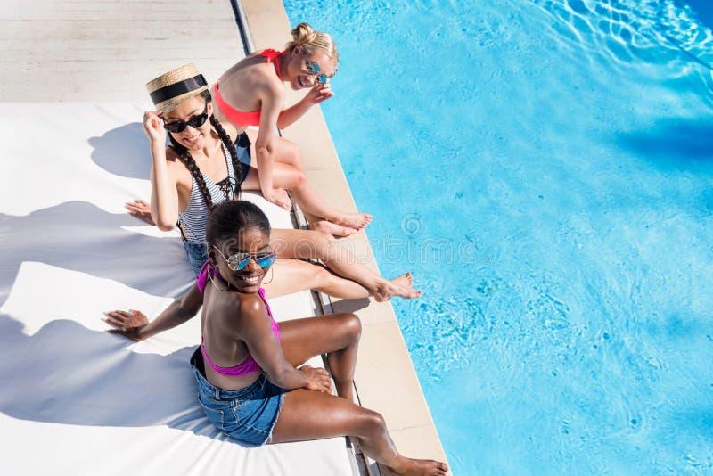 Junge schöne multiethnische Frauen, die am Poolside sitzen lizenzfreie stockbilder