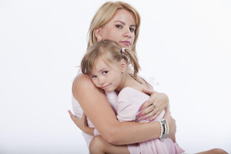 Junge schöne Mutter, die ihre Tochter umarmt lizenzfreies stockfoto