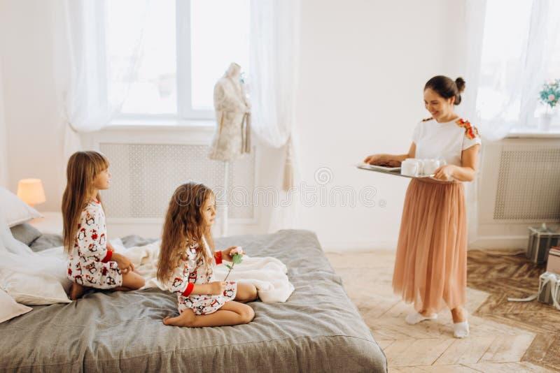 Junge schöne Mutter holt ihren Töchtern Kakao mit Eibischen und Plätzchen, die auf dem Bett im vollen sitzen stockfotos