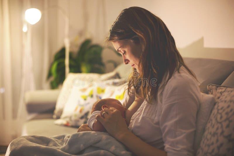 Junge schöne Mutter, ihr neugeborenes Baby an Ni stillend lizenzfreies stockfoto