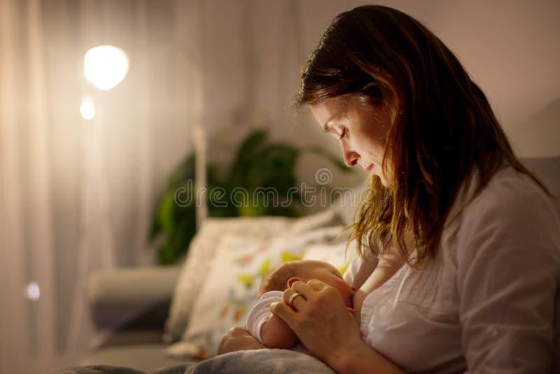 Junge schöne Mutter, ihr neugeborenes Baby an Ni stillend stockfotografie