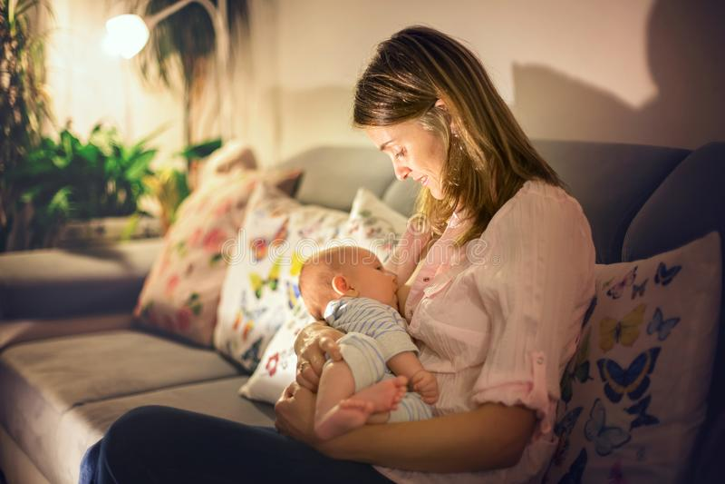 Junge schöne Mutter, ihr neugeborenes Baby stillend stockfotografie