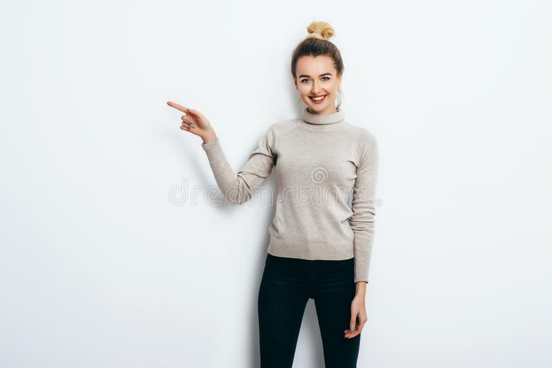 Junge schöne nette Frau mit dem Haarbrötchen, das in den Jeans und in der Strickjacke zeigend mit dem Zeigefinger auf Kopienraum  lizenzfreie stockfotografie