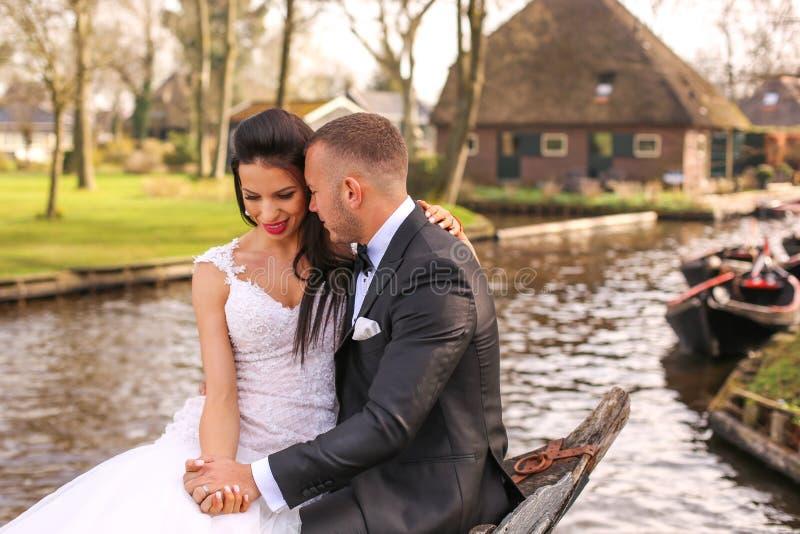 Junge schöne Paare auf einem Boot auf einem Fluss lizenzfreies stockbild