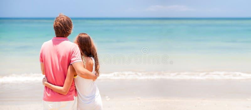 Junge schöne Paare auf tropischem Strand lizenzfreie stockbilder