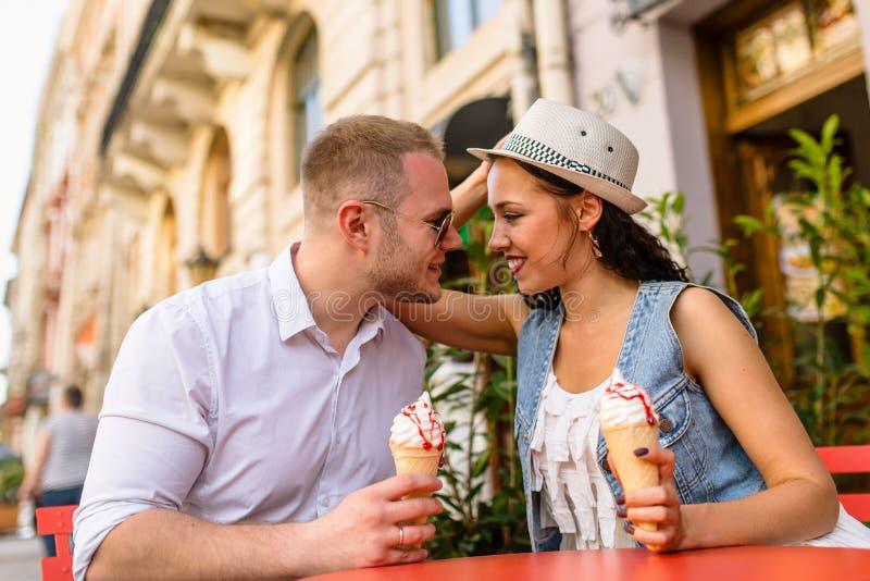 Junge schöne Paare in der Liebe, die Eiscreme isst stockbild