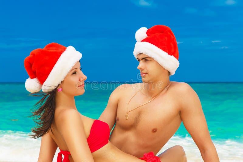 Junge schöne Paare in der Liebe, die Spaß in den Wellen hat, kleideten i lizenzfreie stockfotografie