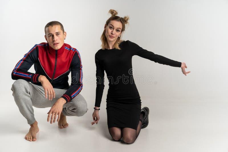 Junge schöne Paare, die auf dem Boden, Studioporträt sitzen lizenzfreies stockfoto