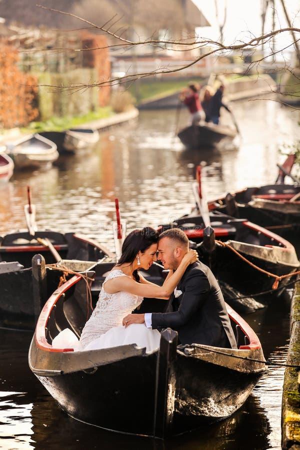 Junge schöne Paare, die auf einem Boot auf einem Fluss aufwerfen lizenzfreie stockbilder