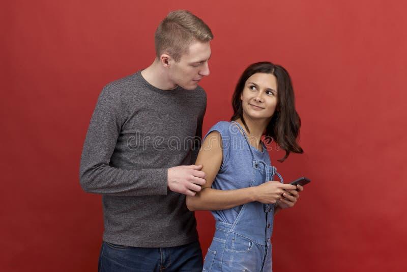 Junge schöne Paare, die auf einem roten Hintergrund stehen Brunettemädchen, das am Telefon simst stockbild