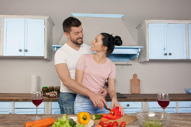 Junge schöne Paare, die in der Küche zusammen kocht einen Salat umarmen Sie l?cheln an einander stockfotografie