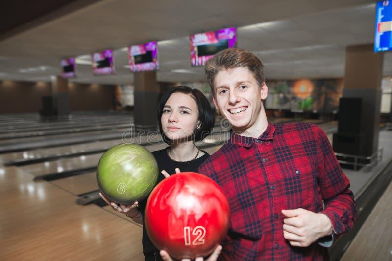 Junge schöne Paare, die mit Bällen auf der Bowlingbahn aufwerfen Spielbowlingspiel des jungen Mannes und des Mädchens stockfoto