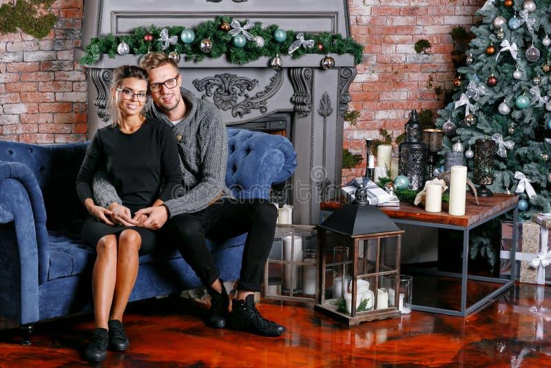 Junge schöne Paare im Dachbodenraum mit Backsteinmauer Glückliches neues Jahr Verzierter Weihnachtsbaum stockfotografie