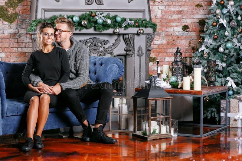 Junge schöne Paare im Dachbodenraum mit Backsteinmauer Glückliches neues Jahr Verzierter Weihnachtsbaum lizenzfreies stockbild