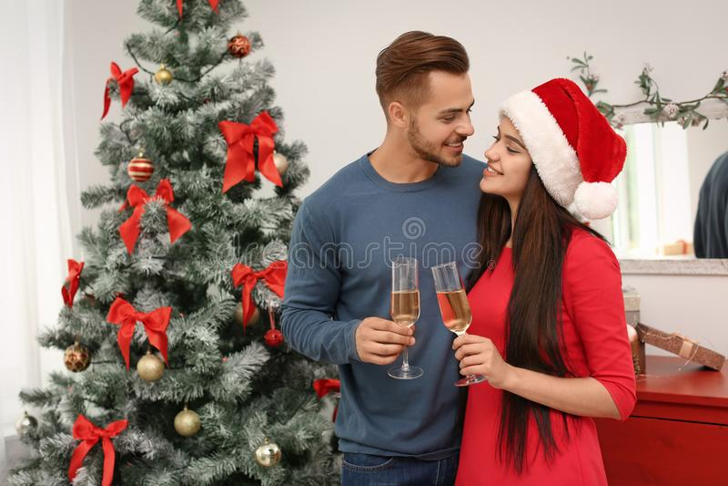 Junge schöne Paare mit Gläsern Champagner nahe Weihnachtsbaum lizenzfreie stockbilder