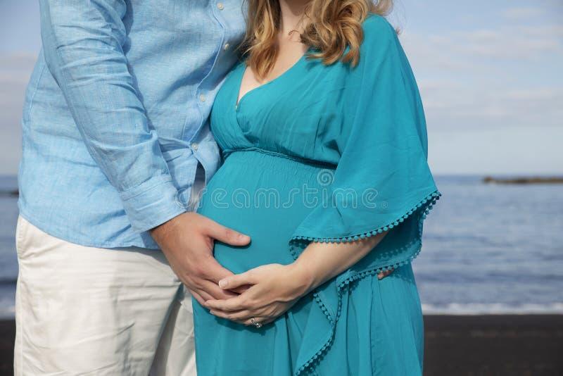 Junge schöne Paare am Ozean, Mann, der den schönen runden Tummy der schwangeren Frau hält lizenzfreies stockbild