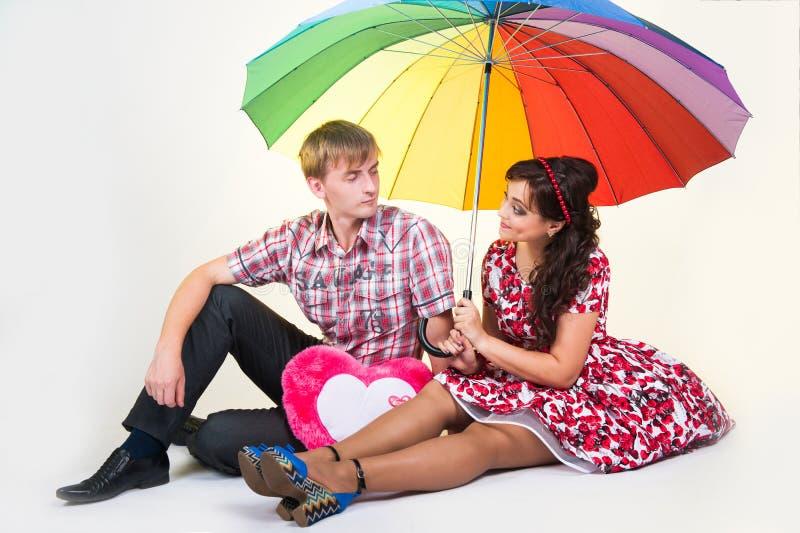 Junge schöne Paare unter buntem Regenschirm stockbilder