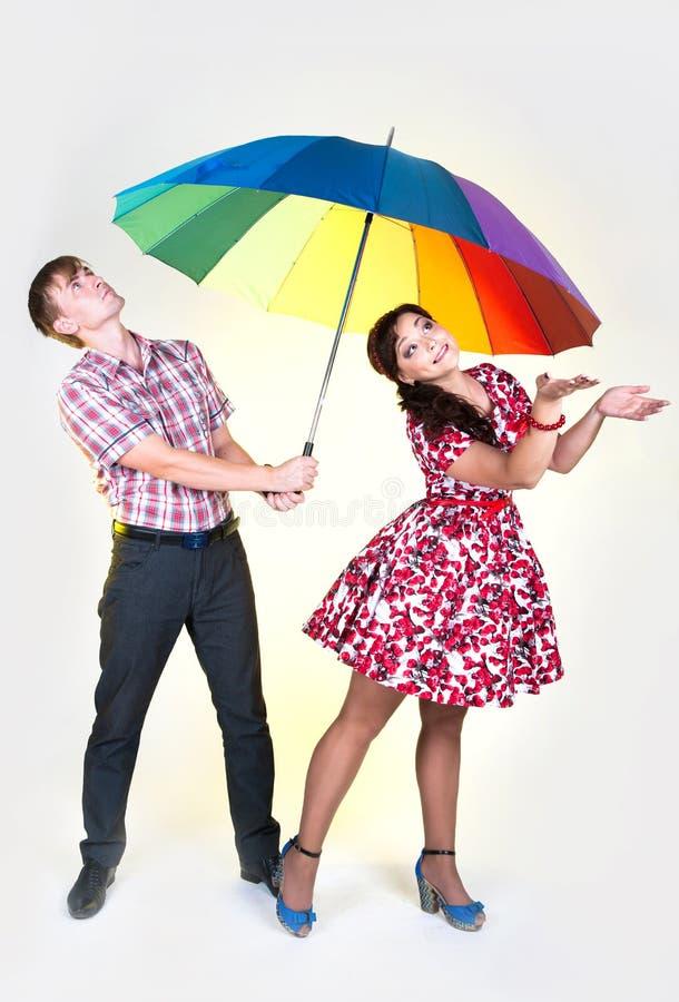 Junge schöne Paare unter buntem Regenschirm lizenzfreie stockbilder