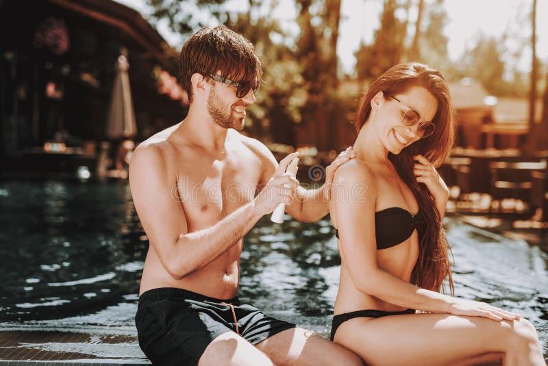Junge schöne Paare unter Verwendung des Lichtschutzes am Poolside lizenzfreies stockfoto